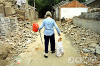 An elderly Chinese woman with bound feet walks through the rubble of demolished homes in a 'hutong' or lane.