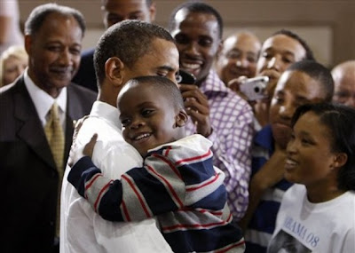 Obama and a little boy sharing a great big hug .