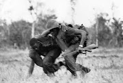 A marine helps his wounded comrade to cover despite North Vietnamese fire .