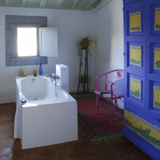 Retro-style-luxury-bathroom-with-center-bathtub-blue-bathrobe-and-pink-chair