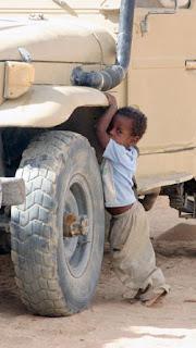 Bambino africano appoggiato alla ruota di un fuoristrada