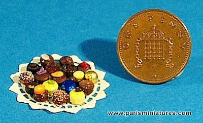 miniature chocolates, some topped with coffee grains, pistachio, sugared violets and some wrapped in foil