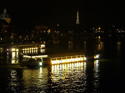 The Seine river at night with a Bateau Mouche and the Eiffel Tower flashing in the background