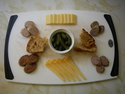 A charcuterie platter featuring homemade weisswurst, kielbasa, duck sausage, and merguez with Sylvan Star cheese