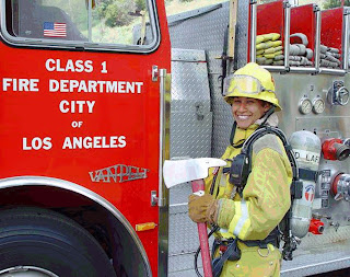 Los Angeles Firefighter Jaime L. Foster standing beside an LAFD Fire Engine holding an axe. Click to learn more...