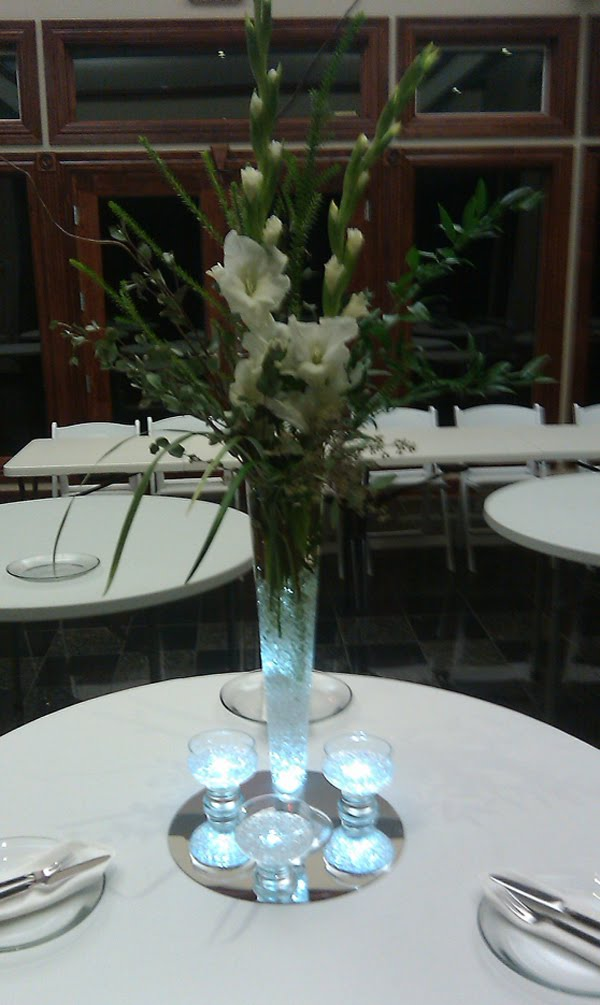 An arrangement of white gladiolus lily grass seeded eucalyptus and Italian