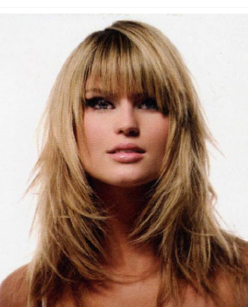 woman with shoulder length blond layered hair and bangs