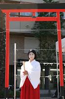 Miko, sacerdotisa shinto posando con torii
