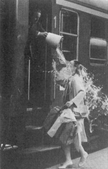 Lady Getting Splashed By Bucket of Water as She Tries to Board Train
