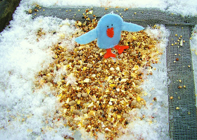 Photography example of one of my bluebird finger puppet crafts sitting on the bird feeder table in the backyard