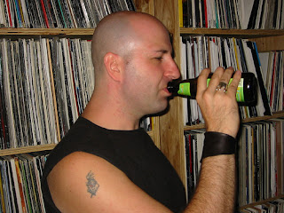 man drinking beer; record collection in background