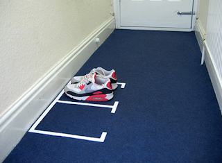 white markers on blue carpet, showing where shoes go