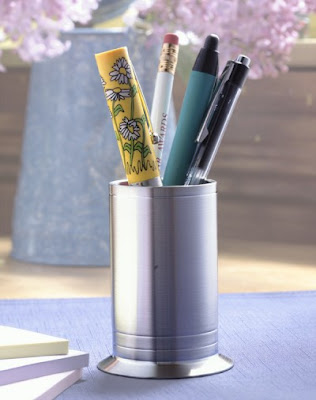 pewter pencil holder, filled with a pencil and some pens