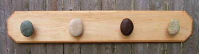 wood coat rack with 4 stones serving as hooks