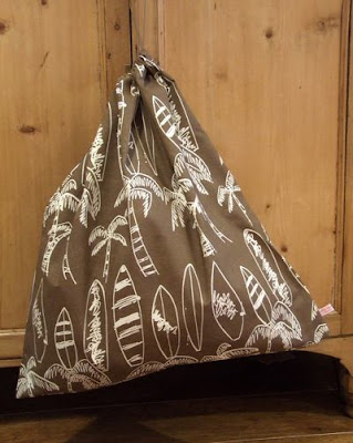 laundry bag, brown, with pictures of surfboards and palm trees drawn in white