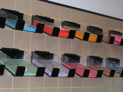 trays of colored paper attached to the wall