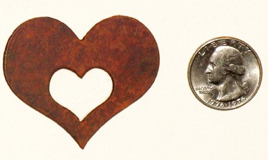 heart-shaped magnet, next to a quarter, for sizing