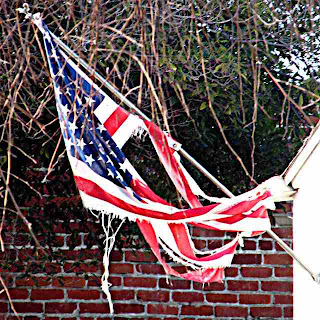 Tattered American Flag displayed in my neighborhood