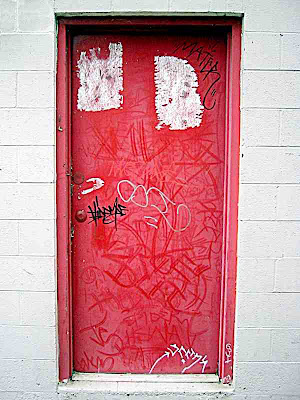 a red door with graffiti on it near a frame store in Pasadena
