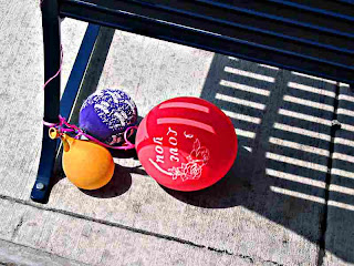 3 mostly deflated balloons under a bench