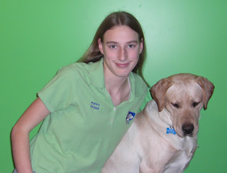 Picture of Toby & I, I'm wearing my green puppy raiser shirt, Toby is looking really bored, the lime green wall is the background