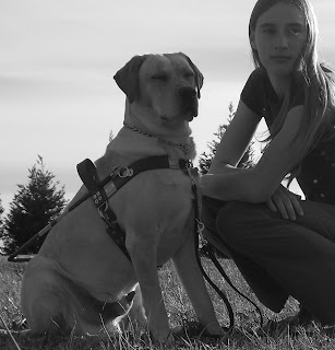 Picture of Toby and I, Toby is 10 months old and wearing the harness, this is a black/white picture taken in my yard, we are both gazing past the camera