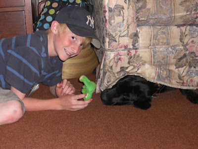 Picture of one farm camper smiling at the camera while holding Rudy's toy. Rudy's head is sticking out from under the couch trying to reach the toy