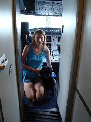 Picture of Rudy & I, Rudy's in a sit-stay, and I'm kneeling down beside him - we are in the cockpit