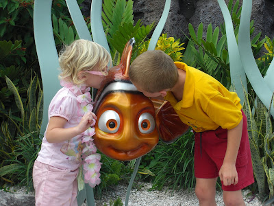 Picture of my 2 cousins kissing a statue of Nemo