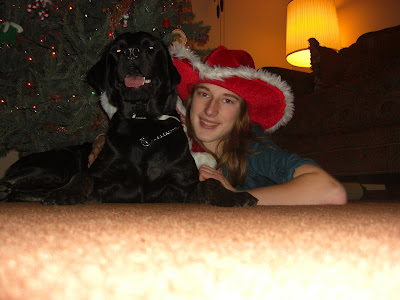 Picture of Rudy & I laying in front of the Christmas tree - both of us are wearing Santa hats