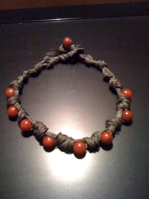 Girocollo di cotone cerato verde scuro con perle di vetro amaranto