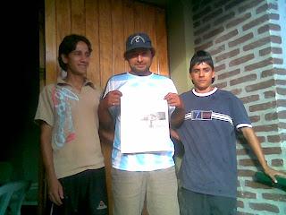 Cesar, Ignacio y Juan, en la puerta de la Capilla Nuestra Señora de Itatí, presentando el periódico que publicó la nota. Si desea contactarnos HAGA CLIC AQUÍ
