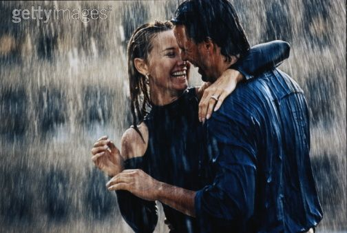 romantic couple kissing in the rain. a couple kissing in the rain.