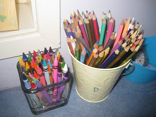 crayons in a square glass container and colored pencils in a cream-colored bucket