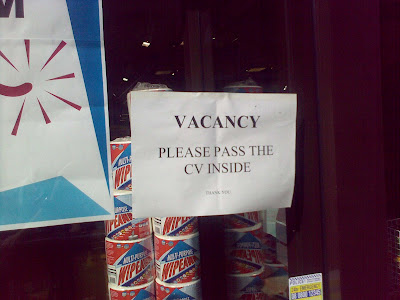 A printed sign in a shop window reading 'VACANCY  PLEASE PASS THE CV INSIDE  THANK YOU'