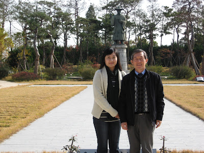 Miss Cho and Mr Lee in front of statue of first Korean Catholic Saint