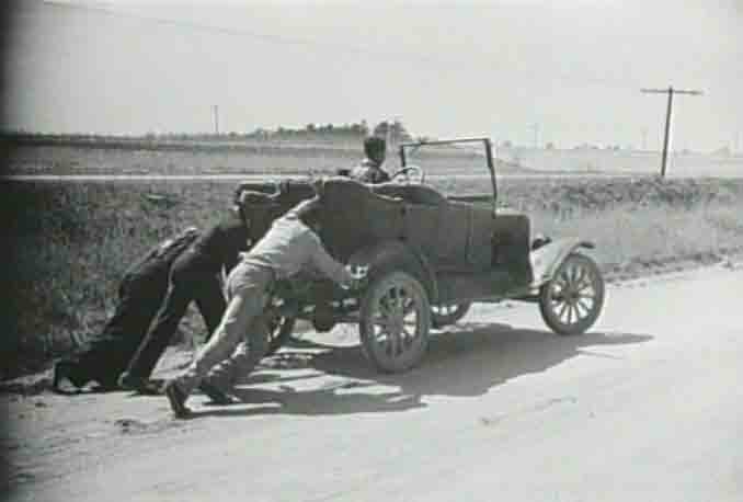 three guys pushing an old car