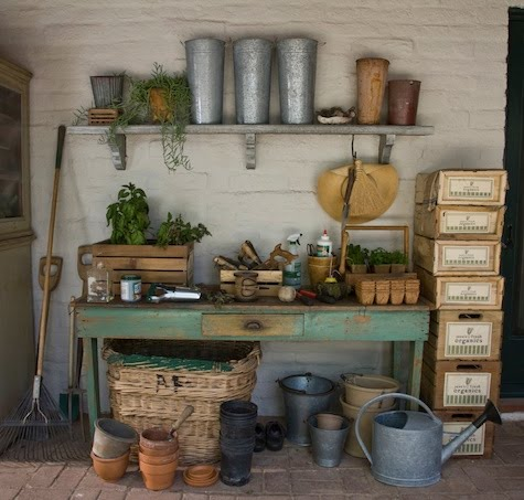 shabby chic style potting bench filled with hand tools and herbs