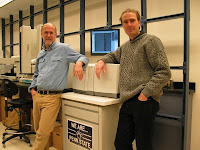 Penn State genomicists Webb Miller and Stephan C. Schuster in front of the Roche/454 Life Sciences' Genome Sequencer 20 System that was used to sequence mammoth DNA. Credit: Penn State University.