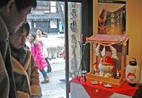 「ひこにゃん」がまつられた神棚に初詣でする観光客(彦根市・夢京橋あかり館)