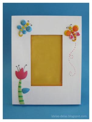 Moldura foto 10x15 na vertical,pintada de branco com aplicação de duas borboletas, uma no canto superior direito a outra no canto superior esquerdo e uma tulipa. as borboletas têm asas redondas, uma em tons de azul com bolinhas amarelas e corações azuis, a outra é amarela, laranja e rosa, com bolinhas amarelas e corações rosa. os corpos são amarelos com riscas azuis ou rosa. as cabeças amarelas têm antenas de arame enrolado. a tulipa é cor de rosa escura com estames negros em arame, o caule é verde claro com riscas verde escuro, e uma folha em azul. uma linha ondulante tracejada em rosa escuro traça um caminho da borboleta