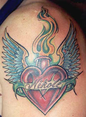 Tatuagem de Coração alado que solta chamas em uma das veias principais (aorta) com o nome da pessoa amada