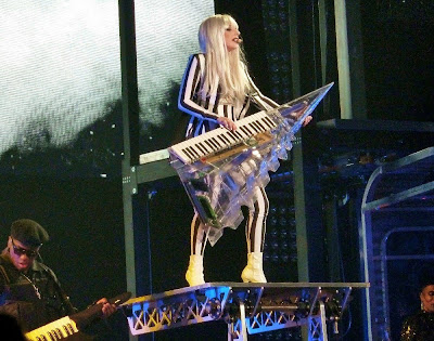 Picture of Lady Gaga dressed in black and white vertical stripes performing