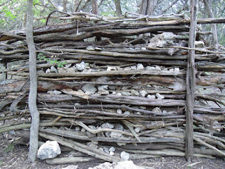 wall made out of sticks and stones, branches and logs
