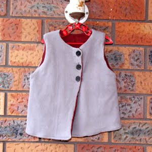 A grey vest, lined in maroon, with three large black buttons reaching from the neck to the bottom of what would be the wearer's chest. It is hanging in front of a brick wall.