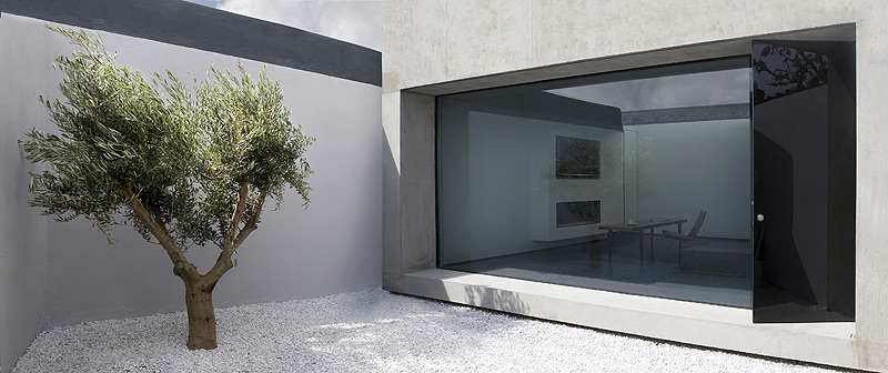Una casa un patio un olivo por odos architects for Casa minimalista interior cocina