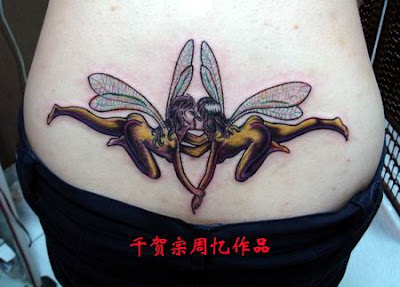 A lower back tattoo showing two fairies kissing.