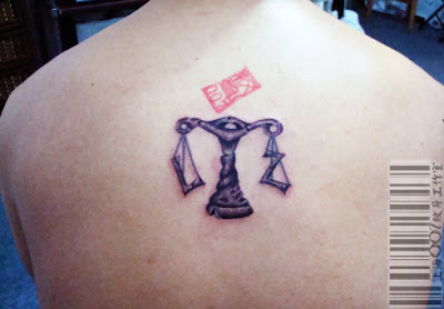 a Libra tattoo design variation on the back with girlfriend's initial on the two sides of the scale
