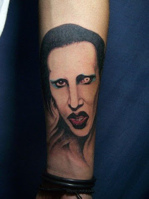 A portrait tattoo on the arm featuring a man with one fake eye.