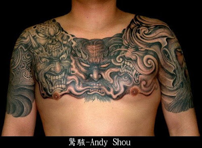 Demon faces tattoo on the chest and shoulder